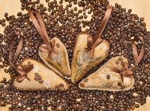 Quatro decoraram corações com fitas e feijões de café. Fotografia de Stock Royalty Free