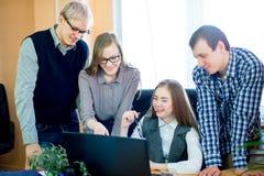 Quatro empregados que olham o portátil Fotos de Stock