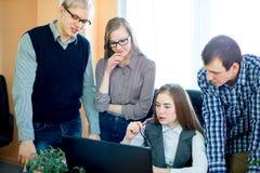 Quatro empregados que olham o portátil Fotografia de Stock