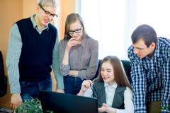 Quatro empregados que olham o portátil Fotografia de Stock Royalty Free