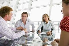 Quatro empresários em uma sala de reuniões fotografia de stock