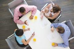Quatro empresários na sala de reuniões com um bebê fotografia de stock