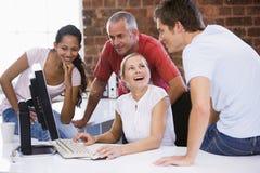 Quatro empresários no espaço de escritórios com computador Imagem de Stock Royalty Free