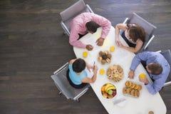 Quatro empresários que comem na tabela da sala de reuniões Imagem de Stock