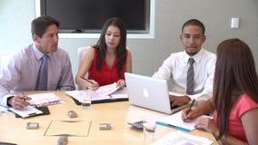 Quatro empresários que têm a reunião em torno da tabela da sala de reuniões filme