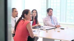 Quatro empresários que têm a videoconferência na sala de reuniões video estoque