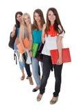 Quatro estudantes fêmeas em seguido Fotografia de Stock Royalty Free