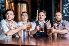 Quatro executivos bem sucedidos que bebem a cerveja e exultam e sh fotos de stock