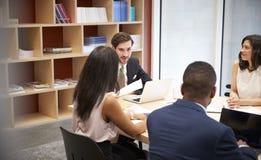 Quatro executivos em uma reunião da sala de reuniões imagens de stock royalty free