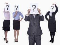 Quatro executivos que sustentam o papel com ponto de interrogação, cara obscurecida, tiro do estúdio Fotos de Stock Royalty Free