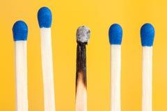 Quatro fósforos e um queimados Fotografia de Stock