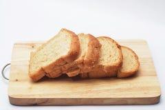 Quatro fatias de pão na placa de corte de madeira no fundo branco Fotografia de Stock Royalty Free