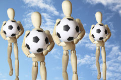 Quatro figuras de madeira com bolas de futebol Fotos de Stock