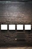 Quatro frames vazios na parede de tijolo Imagem de Stock