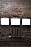 Quatro frames vazios na parede de tijolo Fotografia de Stock Royalty Free