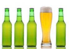 Quatro frascos de cerveja verdes e vidro cheio Foto de Stock
