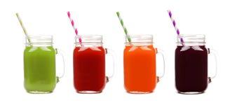 Quatro frascos de pedreiro do suco vegetal, dos verdes, do tomate, da cenoura e da beterraba, isolados Fotos de Stock Royalty Free