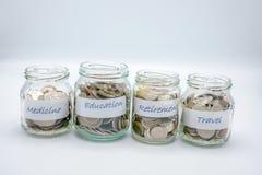 Quatro garrafas de vidro encheram-se com as moedas com papel de etiqueta da medicina, educação, aposentadoria, curso imagens de stock royalty free