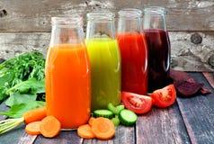 Quatro garrafas do suco vegetal saudável com um fundo de madeira rústico Imagens de Stock
