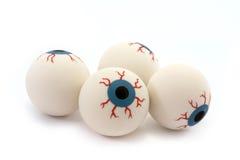 Quatro globos oculares de borracha do brinquedo isolados no branco Fotos de Stock