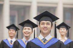 Quatro graduados de sorriso da universidade nos vestidos e nos barretes da graduação, olhando acima imagem de stock