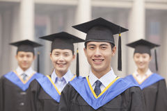Quatro graduados de sorriso da universidade nos vestidos e nos barretes da graduação, olhando a câmera Imagem de Stock Royalty Free