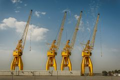 Quatro grandes guindastes amarelos no porto de Huelva, Espanha Imagens de Stock