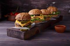 Quatro Hamburger caseiros na tabela de madeira fotografia de stock royalty free