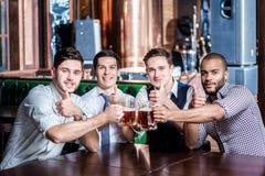 Quatro homens de negócios bebem a cerveja e exultam-na junto na barra che imagens de stock royalty free