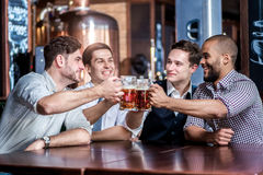 Quatro homens de negócios bebem a cerveja e exultam-na junto na barra con imagens de stock