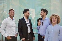 Quatro homens de negócios que estão junto de riso imagens de stock