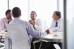 Quatro homens de negócios que têm a reunião em torno da tabela da sala de reuniões imagem de stock