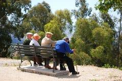Quatro homens espanhóis idosos em um banco fotografia de stock