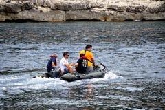 Quatro homens no mar em um barco de motor inflável pequeno Foto de Stock Royalty Free