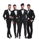 Quatro homens novos elegantes nos smoking que estão junto fotos de stock