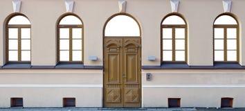 Quatro janelas e uma porta de madeira do carvalho na construção pública renovada Imagem de Stock