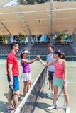 Quatro jogadores de tênis novos que põem as mãos junto antes do dobros combinam fotografia de stock