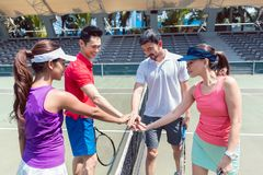 Quatro jogadores de tênis novos que põem as mãos junto antes do dobros misturaram o fósforo foto de stock