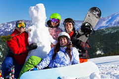 Quatro jovens com snowboard e boneco de neve Foto de Stock Royalty Free