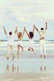 Quatro jovens dois pares que saltam na celebração na praia Imagens de Stock