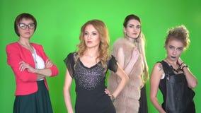 Quatro jovens mulheres bonitas na roupa à moda que levanta na câmera no fundo de tela verde filme