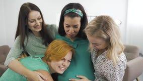 Quatro jovens mulheres caucasianas atraentes abraçando-se e sorrindo Garota ruiva ouvindo a criança na barriga da amiga video estoque