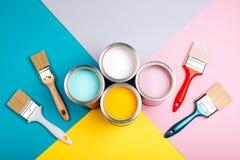 Quatro latas abertas da pintura com as escovas no fundo brilhante fotos de stock