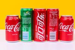 Quatro latas de Coca-Cola e de um podem duende, três latas escritas no chinês imagens de stock royalty free