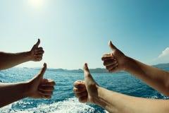 Quatro mãos com um polegar acima, uma vista bonita do mar, umas férias tropicais, uma paisagem e um humor positivo Fotos de Stock Royalty Free