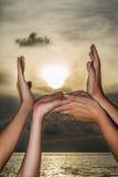 Quatro mãos que tentam alcançar o sol Fotografia de Stock Royalty Free