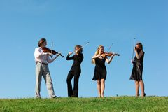 Quatro músicos jogam violinos de encontro ao céu Fotos de Stock Royalty Free