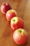 Quatro maçãs na tabela Fotografia de Stock