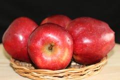 Quatro maçãs vermelhas na placa da palha imagem de stock royalty free