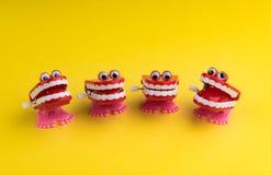 Quatro maquinismo de relojoaria Toy Faces Laughing em um fundo amarelo fotos de stock royalty free